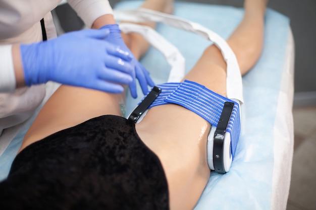 美容院での女性の足の筋刺激の手順。