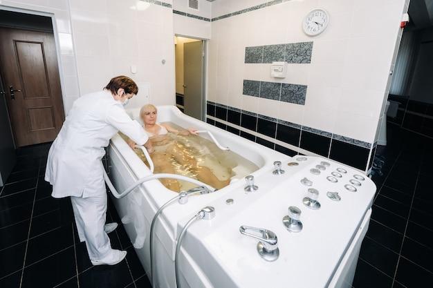 Процедура подводного душа-массажа в ванной. девушка на процедуре подводного массажа.