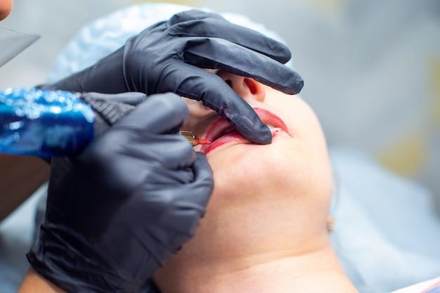 Процесс нанесения перманентного макияжа на губы с помощью тату-машины крупным планом.