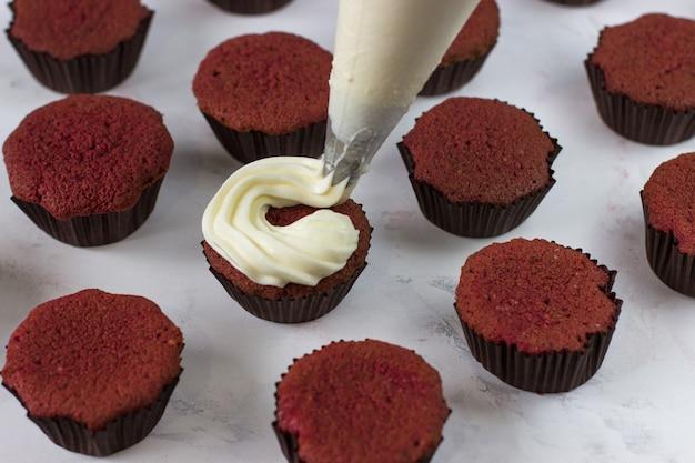 Процесс нанесения крема на кекс красный бархат