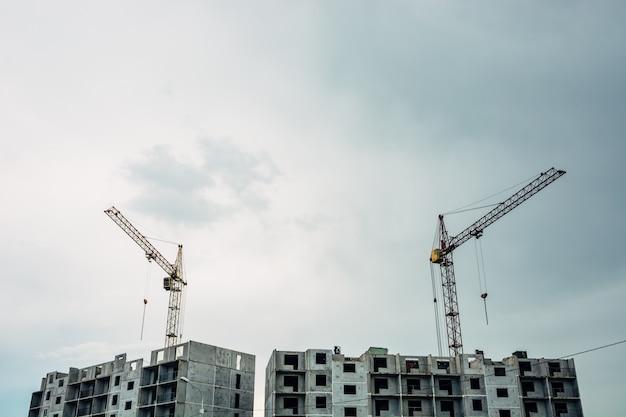 Процесс строительства многоэтажного здания. подъемные краны на фоне неба.