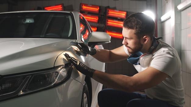 Процесс проверки нанесения нанокерамического покрытия на автомобиль работником мужского пола с использованием фонарика