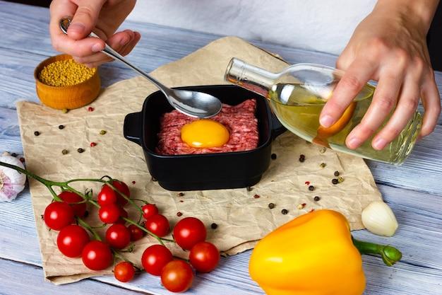 豚肉の細かく刻んだ女性の手から軽い木製のテーブルでカツレツを調理するプロセスは、季節を振りかけます...