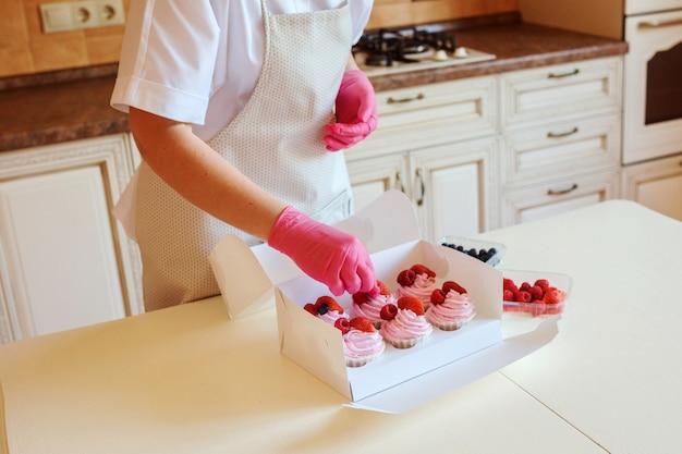 ラズベリーで飾られたホイップフルーツクリームでおいしいカップケーキを調理するプロセス