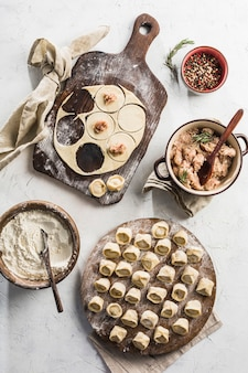 Процесс приготовления пельменей. много готовых к употреблению пельменей со свининой на большой деревянной доске с мукой на светлом фоне.