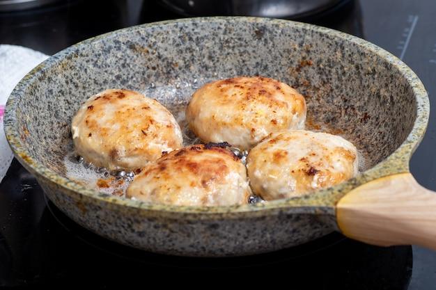 Процесс приготовления на сковороде с жареным мясом, тефтелями, шашлыком. концепция быстрого питания - крупным планом котлет