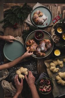 木製のテーブルで小麦粉生地からママと娘の自家製ベーグルを調理するプロセス