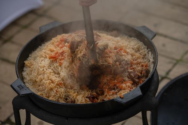 Процесс приготовления плова. национальное блюдо восточной кухни. рис с мясом.