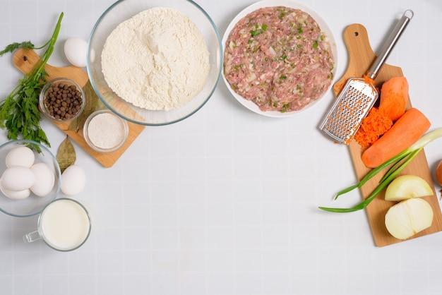 Процесс приготовления узбекских мантов в домашних условиях, ингредиенты - мясо, овощи, тесто. вид сверху на светлом фоне.