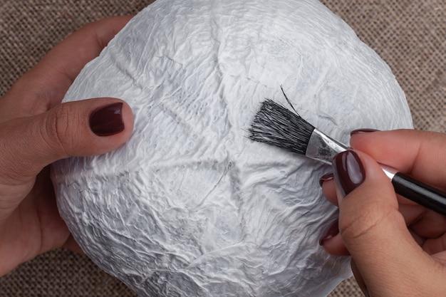 張り子からカボチャを作り、ベースに接着剤を塗るプロセス、ハロウィーンの装飾の趣味。