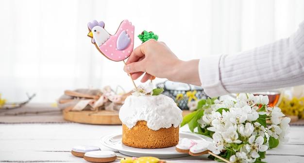 ジンジャーブレッドと花でお祝いのケーキを飾るプロセス。イースター休暇の準備の概念。