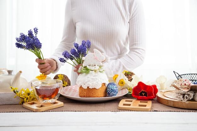 イースターのお祝いのためにお祝いのテーブルを花で飾るプロセス。