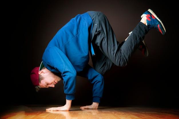 暗いスタジオで若いダンサーがフリーズするプロセスb