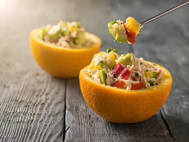 Процесс поедания салата из апельсина, авокадо и курицы вилкой. диетическое питание из тропических фруктов и курицы. Premium Фотографии