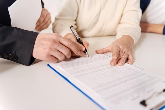 保険に加入するプロセス。家に座って保険証書に署名しながら社会保障顧問と会う年配の毅然とした孤独なカップル