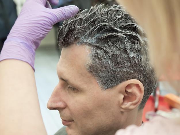 Процесс окрашивания волос на мужчине в салоне красоты. закройте вверх.