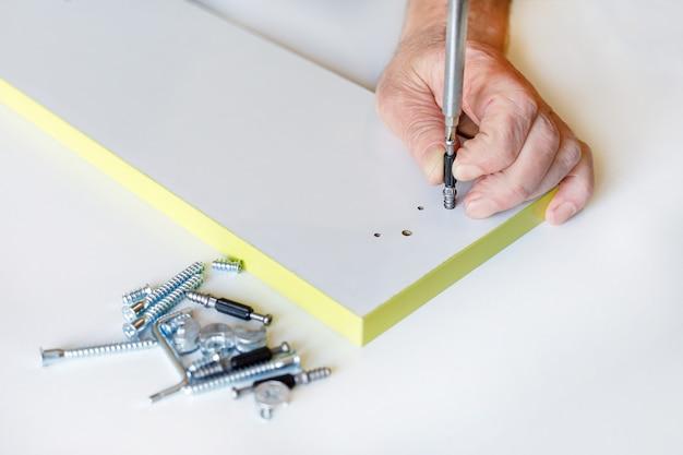 家具の引き出しの正面に留め具を取り付けるプロセス。