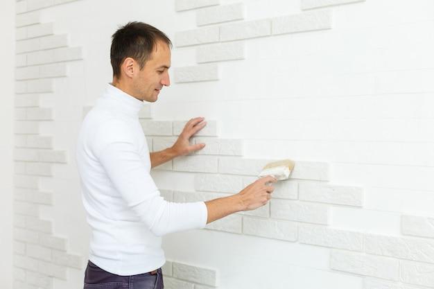 Процесс установки декоративной плитки из песчаника на фундамент дома
