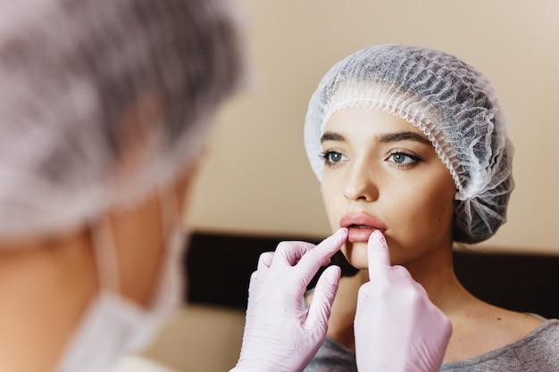 Процесс усиления губ. доктор рассматривает усиленные губы. молодая девушка с красивым лицом в специальной шляпе и руки доктора в розовых перчатках.