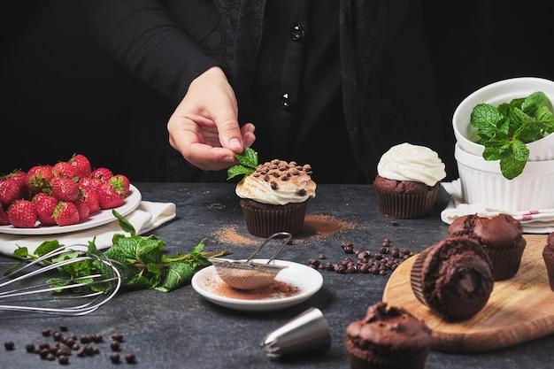 Процесс приготовления кексов. руки повара в кадре. десерт со сливками, свежими ягодами, шоколадом и мятой. кексы с начинкой из шоколадного ганаша.