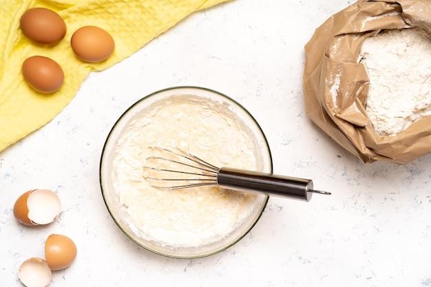 Процесс приготовления теста для блинов с ингредиентами на светлом столе, яйца и мука взбиваются миксером.