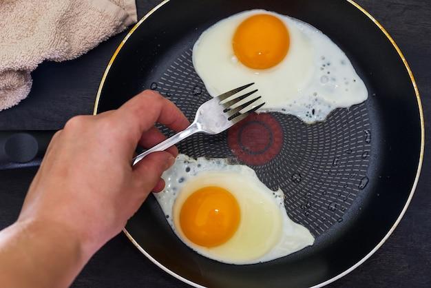 2個の卵から目玉焼きを作るプロセス。手がフォークで鍋の卵を回します。