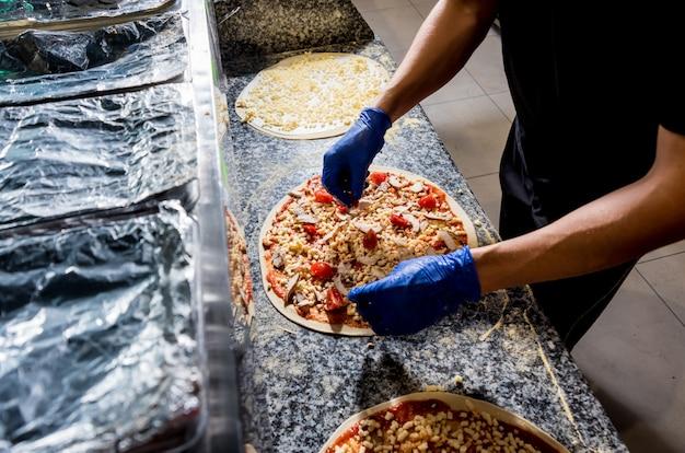 Процесс приготовления пиццы. руки шеф-пекаря, делая пиццу на кухне кафе
