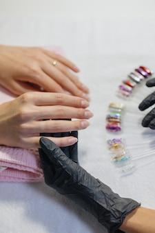 Процесс маникюра в студии или салоне красоты для женщин делает мастер маникюра и педикюра.