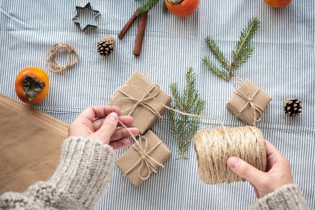 Процесс упаковки стильных современных подарков на рождество и новый год. подарочные коробки из крафт-бумаги, шпагата и веток елки. рождественский фон, атмосфера праздника.