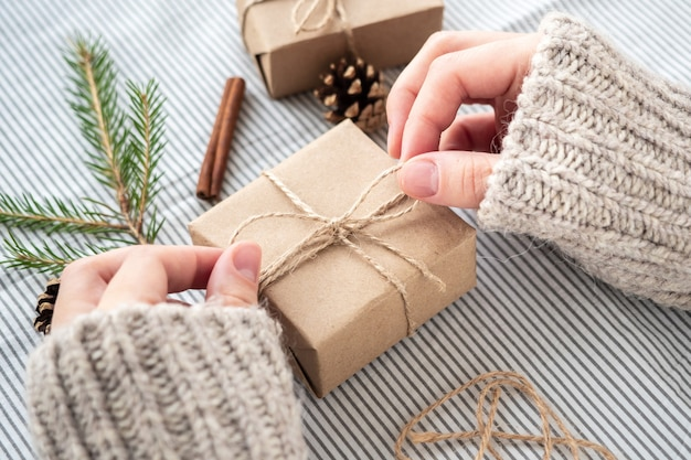 Процесс упаковки стильных современных подарков на рождество и новый год. подарочные коробки из крафт-бумаги, шпагата и веток елки.