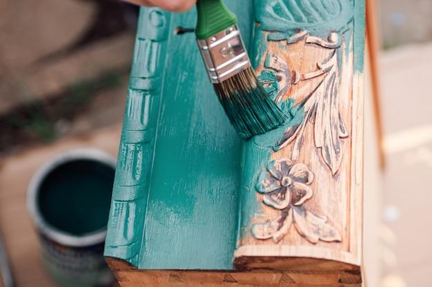 Процесс покраски деревянного ящика комода или стола цветочным узором на открытом воздухе экологичен ...