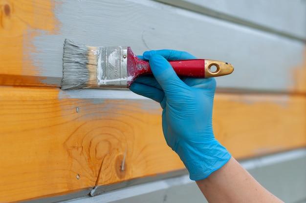 집의 나무 벽을 그리는 과정. 손 클로즈업, 나무 질감 및 페인트에 페인트 브러시