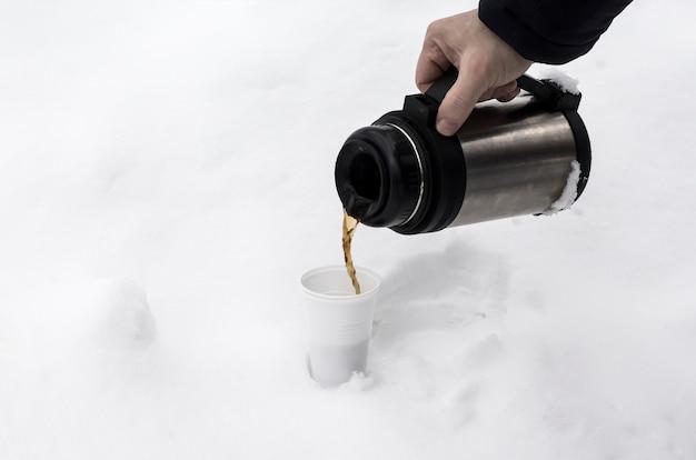 자연의 눈 더미 속에서 겨울에 일회용 유리 잔에 커피를 붓는 과정.