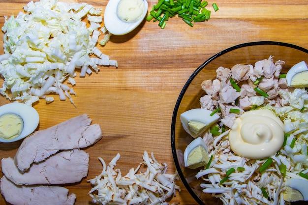 健康的な食事のためにおいしいサラダを準備するプロセス。木製の背景にサラダの材料とナイフ。