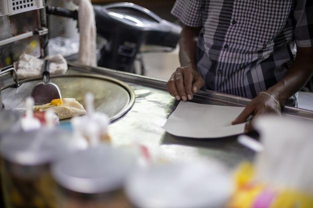 通りのカウンターでおいしい伝統的なタイの春巻きを準備するプロセス。男性の手は油でパンケーキを炒めます。地元の特産品。