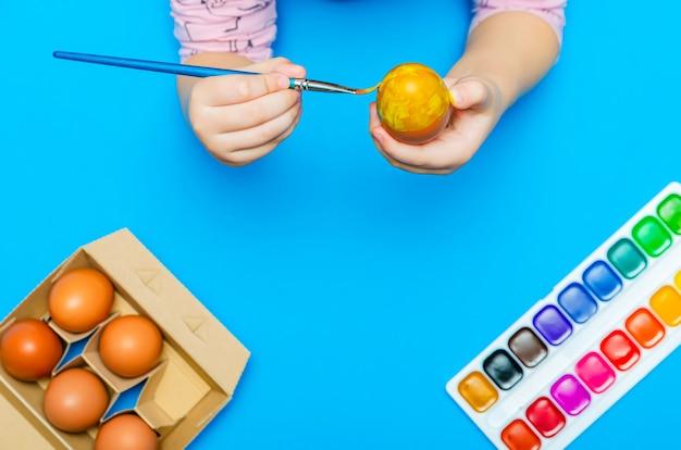 부활절을 준비하는 과정에서 아이는 휴가 전에 브러시로 부활절 달걀을 그립니다. 멀티 컬러 페인트. 공간을 복사하십시오. 프리미엄 사진
