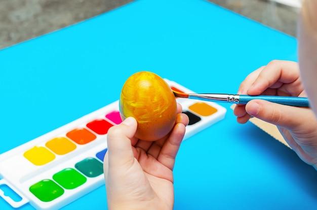 부활절을 준비하는 과정에서 아이는 휴가 전에 붓으로 부활절 달걀을 그립니다. 멀티 컬러 페인트. 공간을 복사합니다.