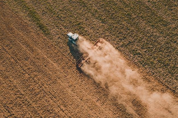 Процесс подготовки земли к посеву культурных растений, вид сверху на поле.