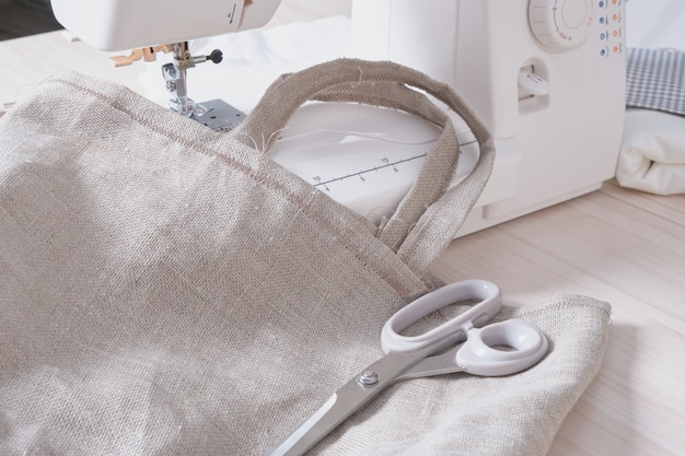 Процесс шитья эко-сумок, ниток, ножниц и швейной машинки на фоне копировального пространства.