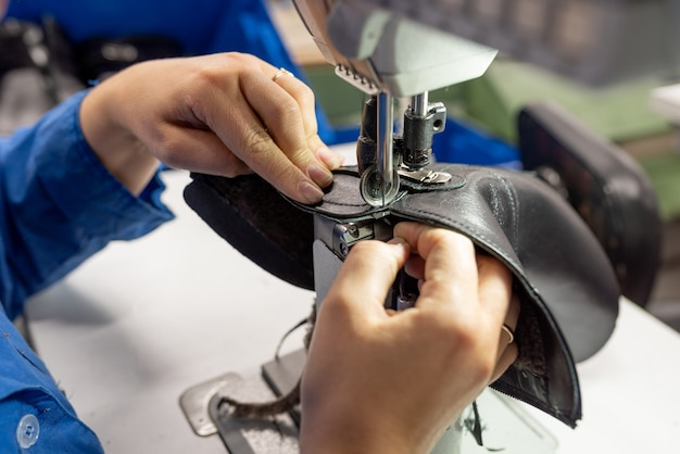 재봉틀에 신발을 재봉하는 과정. 신발 생산. 어떤 목적을 위해.