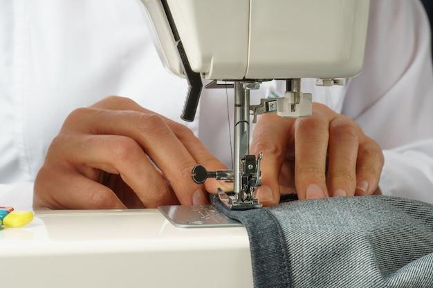Процесс укорачивания джинсовых штанов на швейной машинке