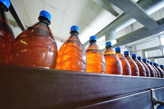 Производство пива. большие коричневые пластиковые бутылки с голубыми крышками с пивом движутся по конвейерной ленте на фоне пивоварни.