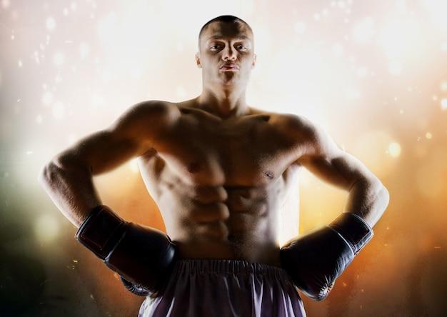 Боксёр-профессионал стоит в боевой стойке и грозно смотрит на противника.