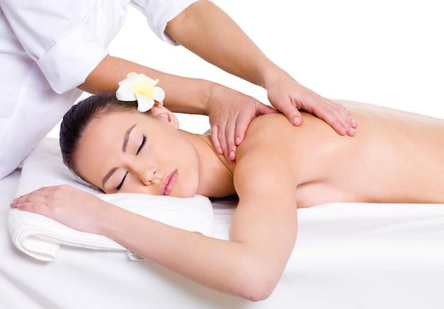 Профессиональный массажист делает расслабляющий массаж спины молодой красивой женщине - белый фон