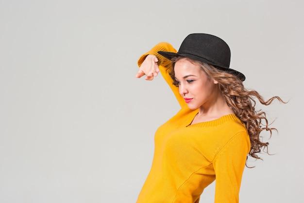 Профиль эмоциональной девушки в шляпе на сером