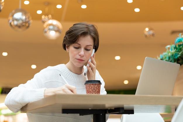 프로그래머는 노트북의 카페에 앉아 메모장에 아래에서 사진을 씁니다. 흰색 스웨터, 프리랜서 개념에 갈색 머리.