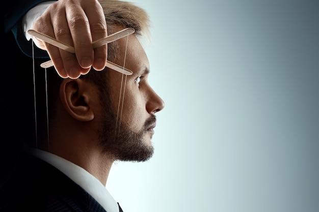 인형극의 남성 손은 인간의 머리 속의 의식을 조작합니다. 세계 음모 개념, 세계 정부, 조작, 통제.