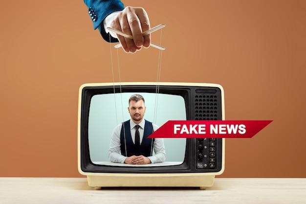 인형극의 남성 손은 뉴스 아나운서, 가짜 뉴스, 속임수를 조작합니다. 그림자 정부, 세계 음모, 조작, 통제, 타블로이드의 개념.