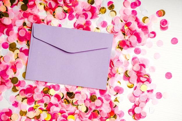 Фиолетовый конверт лежит на фоне разноцветных конфетти, праздничный дизайн.