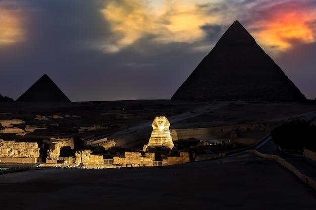 저녁의 피라미드와 스핑크스는 조명을 보여줍니다, 기자.